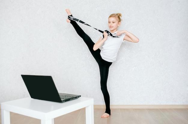 Una studentessa europea fa esercizi di stretching con un elastico e guarda video online su un laptop. ginnastica, coreografia. auto-isolamento, quarantena, formazione online