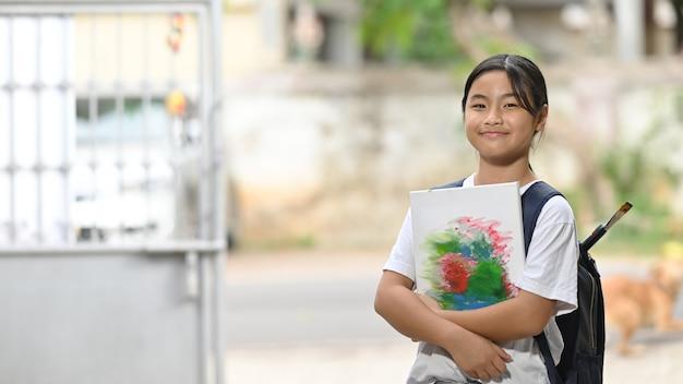Una studentessa tiene in mano l'attrezzatura per dipingere e porta una borsa mentre è in piedi e aspetta uno scuolabus.