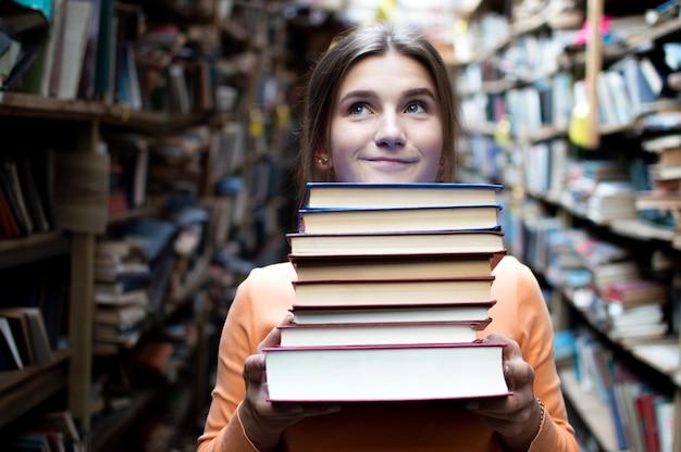 Una studentessa tiene una pila di libri in biblioteca, cerca la letteratura e si offre di leggere, una donna si prepara per lo studio, la conoscenza è potere, il libraio in libreria