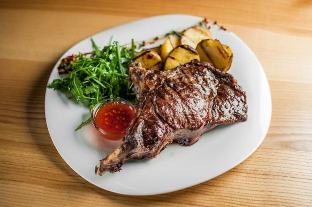 Una succosa, appetitosa bistecca, cotta alla griglia con verdure e salsa su un piatto bianco