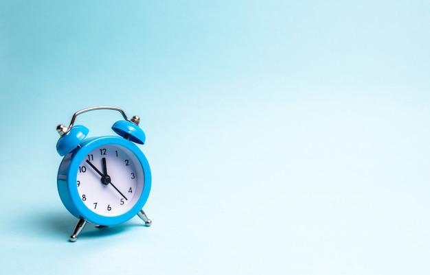 Una sveglia blu su sfondo azzurro. il concetto di aspettare un incontro, una data.