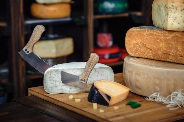 Una tavola di legno con vari tipi di gustosi formaggi sul tavolo con coltelli e verdure