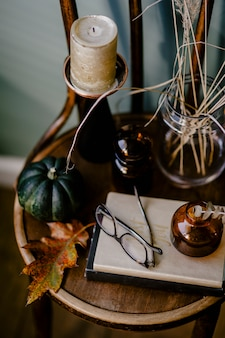 Una tavola di legno decorata con un tema autunnale con una candela aromatica, bicchieri, fiori secchi,
