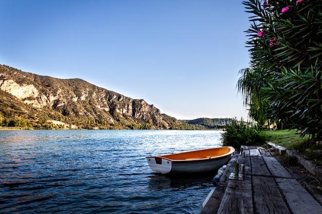 Una tavola legata a un molo di legno sul lago. barca a remi legata ad un molo di legno. calma del lago dei pipistrelli.