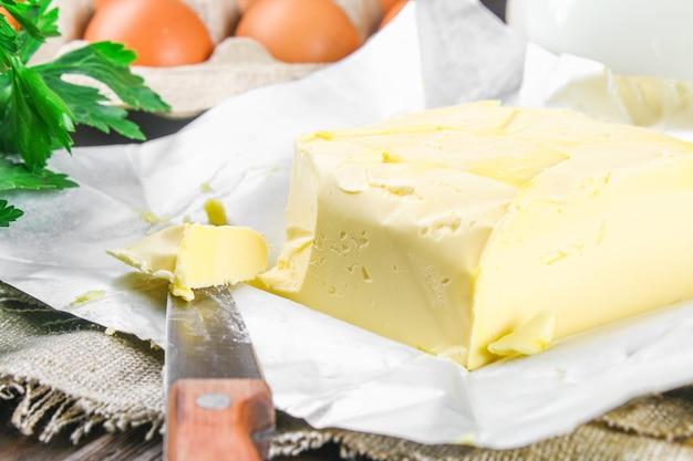 Una tavoletta di burro viene tagliata a pezzi su una tavola di legno