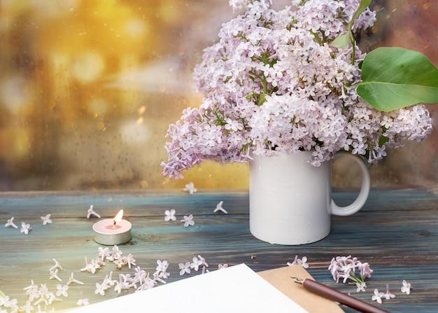 Una tazza bianca con il lillà, una candela e una busta su una superficie di legno d'annata il giorno di pioggia della primavera e il fondo del bokeh.