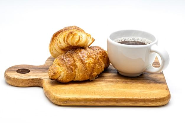Una tazza bianca di caffè caldo con il croissant sull'isolato di legno del vassoio su fondo bianco.