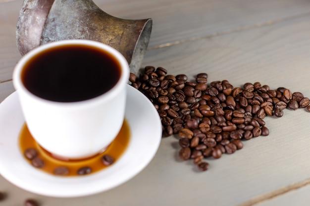 Una tazza bianca di caffè caldo in una dispersione di chicchi di caffè.