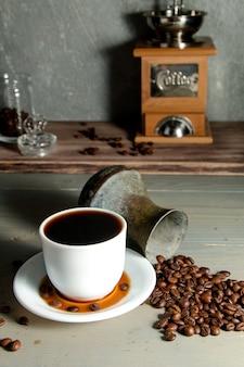 Una tazza bianca di caffè caldo uno scattering di chicchi di caffè su un legno
