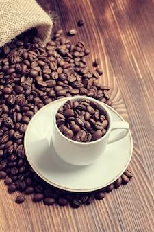 Una tazza bianca sui chicchi di caffè da una borsa tricottata con un fondo di legno bruciato. verticale. tonica.