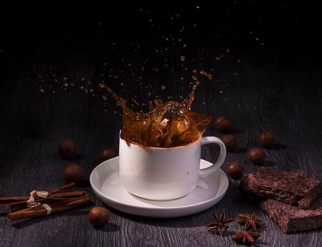Una tazza con spruzzi di caffè con noci e stecca di cannella sul tavolo di legno su sfondo scuro