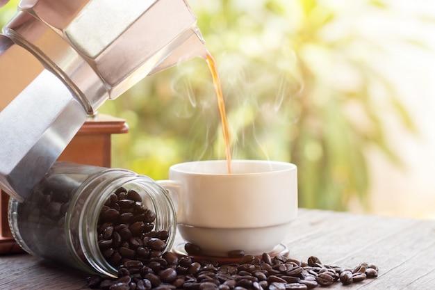 Una tazza delle tazze da caffè calde del caffè espresso e dei chicchi di caffè arrostiti con il vaso di moka disposto sul fondo di legno del pavimento, mattina del caffè, fuoco selettivo