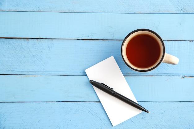 Una tazza di bevanda e un taccuino di carta con una penna nera su un legno blu