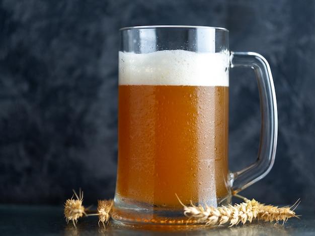 Una tazza di birra di grano non filtrata su uno sfondo di cemento scuro e spighe di grano