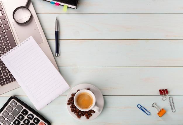 Una tazza di buon caffè al lavoro. taccuino, penna, laptop, calcolatrice, documenti finanziari, una tazza di cappuccino caldo sul tavolo. chicchi di caffè lente di ingrandimento.