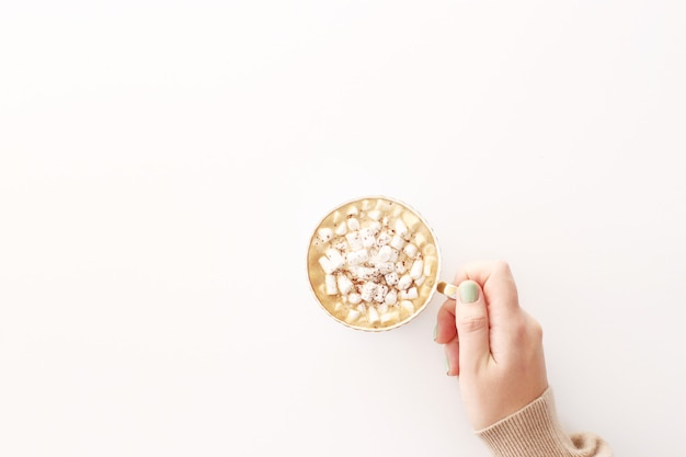 Una tazza di cacao con marshmallow su uno sfondo bianco in una mano femminile