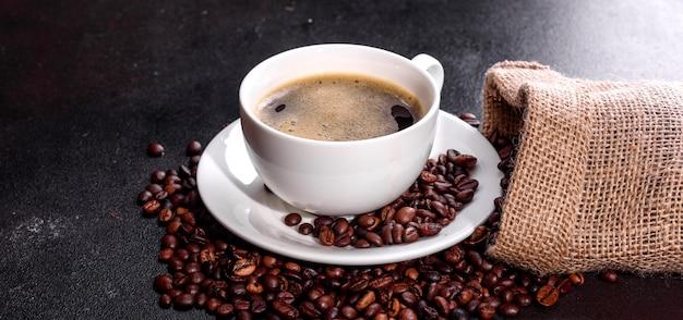 Una tazza di caffè al mattino profumato e fresco per iniziare la giornata in modo allegro. bella tazza di caffè con caffè su un tavolo scuro