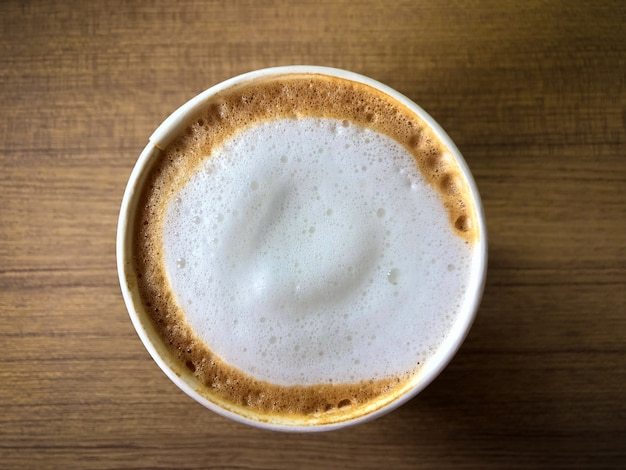 Una tazza di caffè caldo di arte del latte sulla tavola di legno in caffetteria
