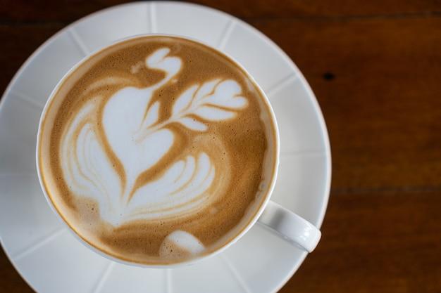 Una tazza di caffè caldo latte art sul tavolo di legno