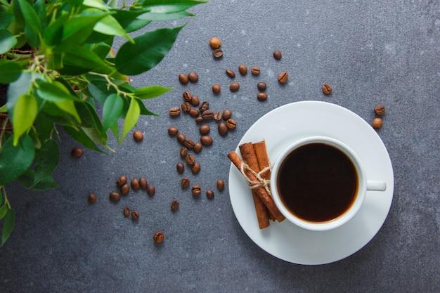 Una tazza di caffè con cannella secca, pianta vista dall'alto su una superficie grigia