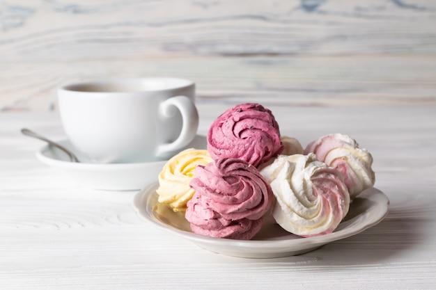 Una tazza di caffè con deliziosi marshmallow fatti in casa di sapori diversi sul tavolo di legno.