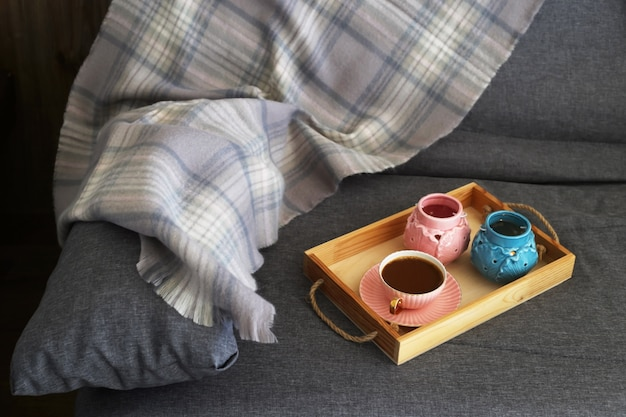 Una tazza di caffè con latte su un vassoio di legno con candele rosa e turchesi