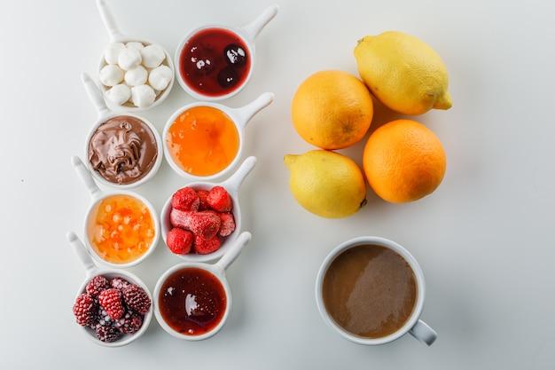 Una tazza di caffè con marmellate, lamponi, zucchero, cioccolato in tazze, arancia e limoni