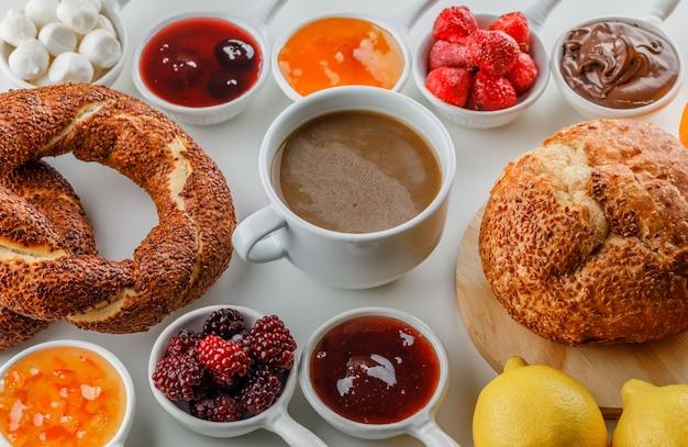 Una tazza di caffè con marmellate, lamponi, zucchero, cioccolato in tazze, bagel turco, pane, arancia e limoni