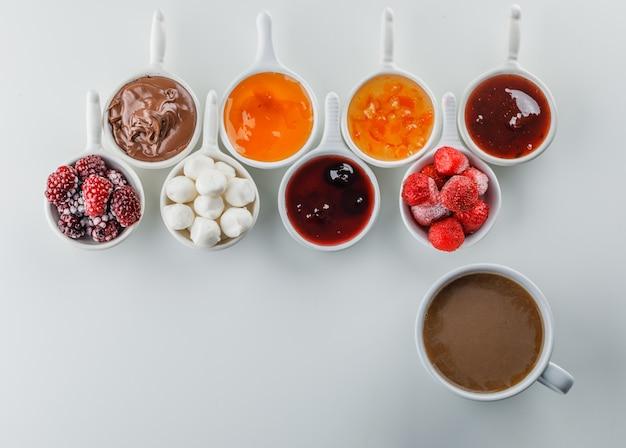 Una tazza di caffè con marmellate, lamponi, zucchero, cioccolato in tazze vista dall'alto su una superficie bianca