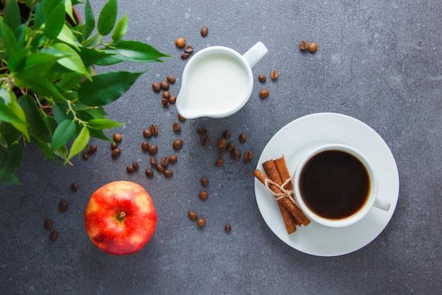 Una tazza di caffè con mela, cannella secca, pianta, latte su superficie grigia, vista dall'alto.