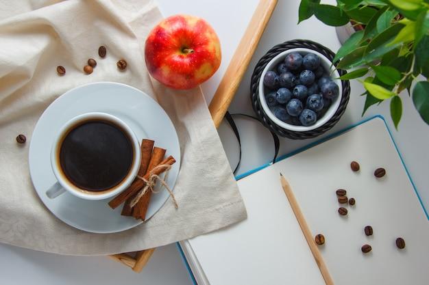 Una tazza di caffè con mirtilli, mela, cannella secca, pianta, matita e taccuino vista dall'alto su una superficie bianca