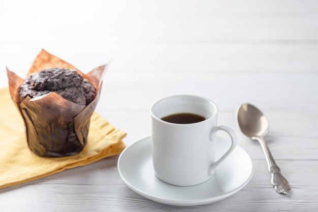 Una tazza di caffè con muffin al cioccolato sul tavolo di legno