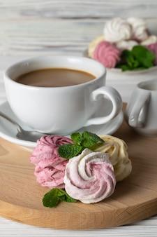 Una tazza di caffè con panna e deliziosi marshmallow fatti in casa di diversi gusti e colori