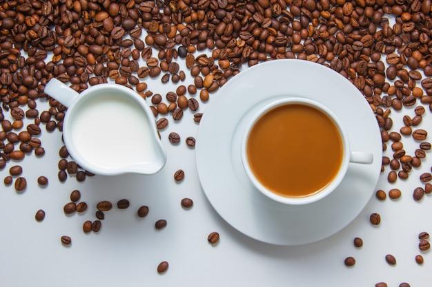 Una tazza di caffè con vista dall'alto di latte con chicchi di caffè sulla superficie