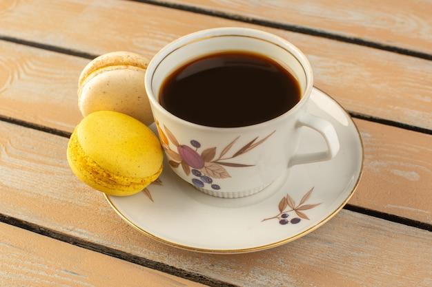 Una tazza di caffè con vista frontale calda e forte con macarons francesi sulla scrivania rustica color crema bere caffè foto forte