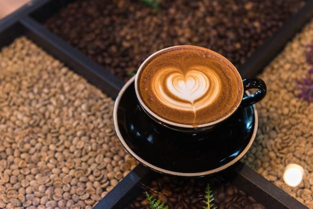 Una tazza di caffè di arte del latte sul tavolo con sfondi di chicchi di caffè