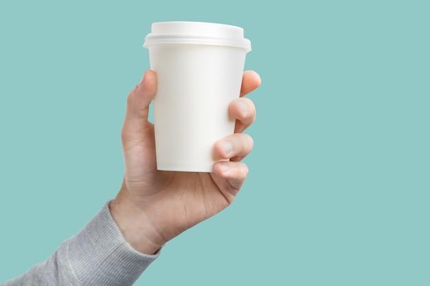 Una tazza di caffè di carta in mano. tazza di caffè del libro bianco a disposizione isolata