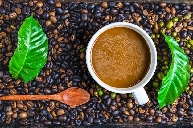 Una tazza di caffè e chicchi di caffè su un tavolo di legno
