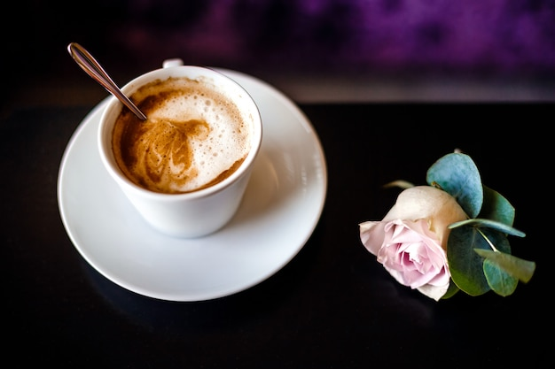 Una tazza di caffè e rosa.