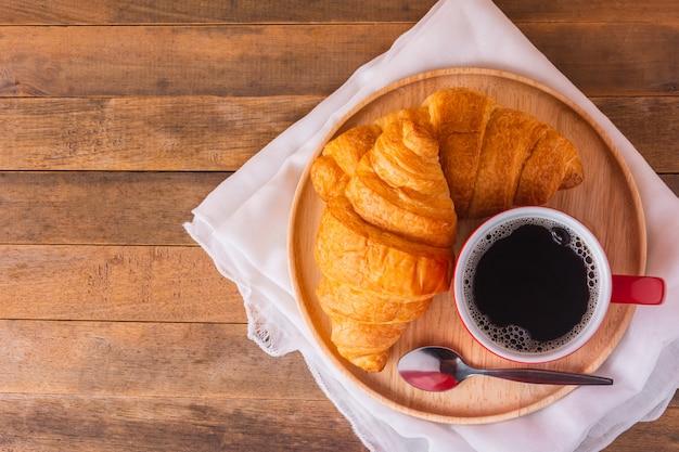 Una tazza di caffè e un pane del croissant sulla tavola di legno, vista superiore con lo spazio della copia