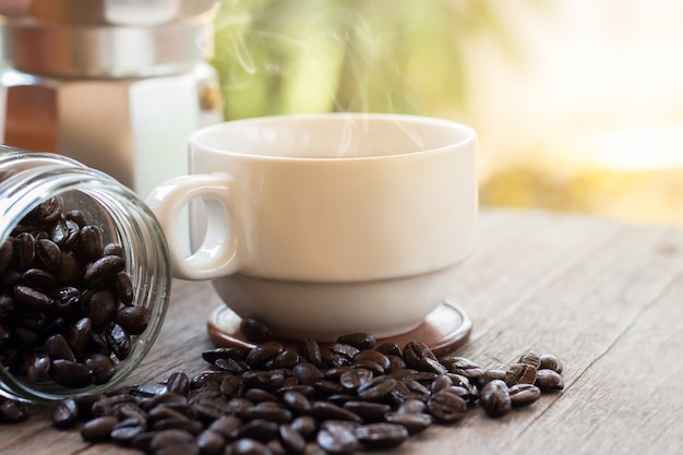 Una tazza di caffè espresso caldo e chicchi di caffè tostati