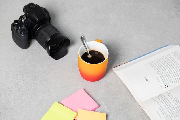 Una tazza di caffè espresso con un buon libro e una macchina fotografica