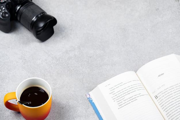 Una tazza di caffè espresso con un libro e una macchina fotografica sul tavolo