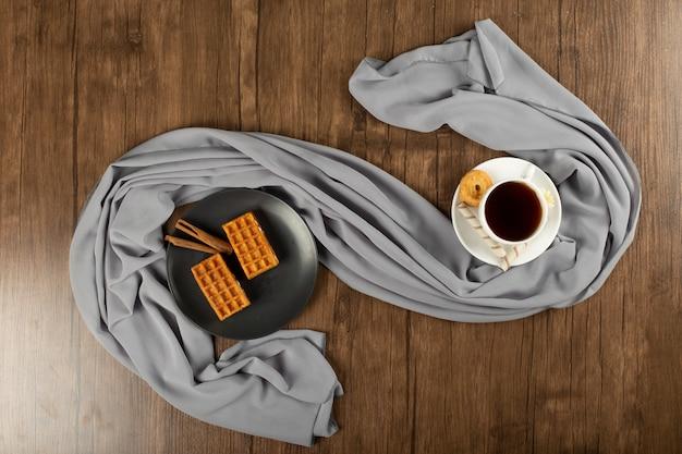 Una tazza di caffè espresso e cialde in piattino nero. vista dall'alto