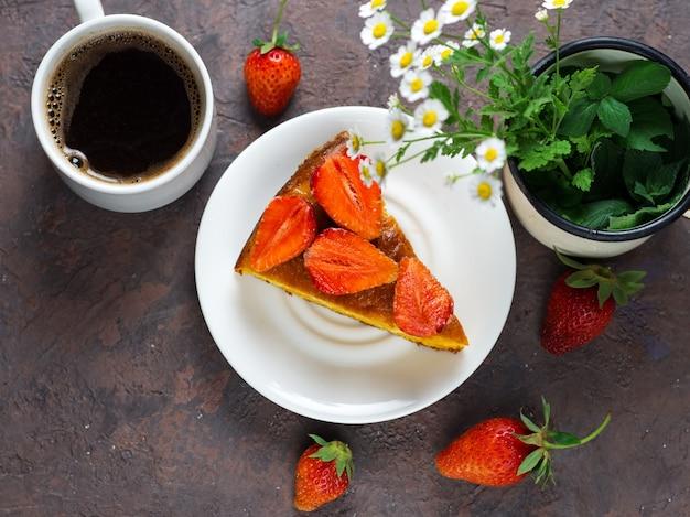 Una tazza di caffè espresso e torta di fragole sul tavolo
