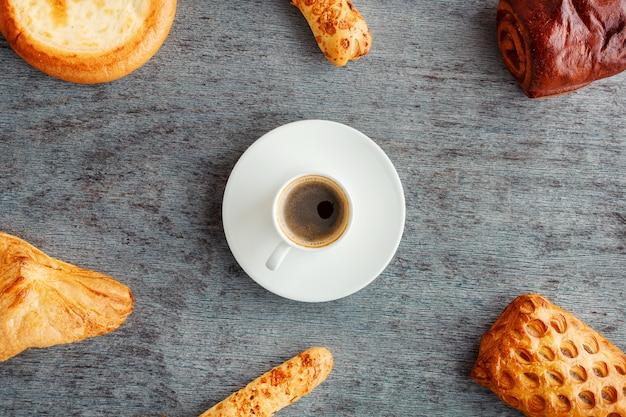 Una tazza di caffè espresso sul piattino, focacce e torte sul tavolo di legno