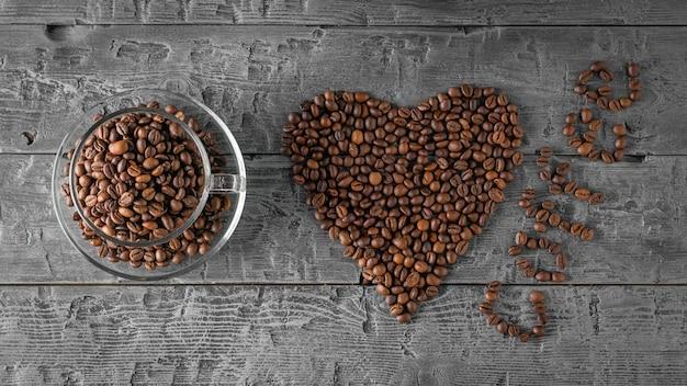 Una tazza di caffè in grani, un cuore di chicchi di caffè e la scritta caffè sul tavolo nero. la vista dall'alto. disteso. cereali per la preparazione della bevanda popolare. disteso.