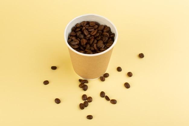 Una tazza di caffè in plastica vista dall'alto con semi di caffè marroni