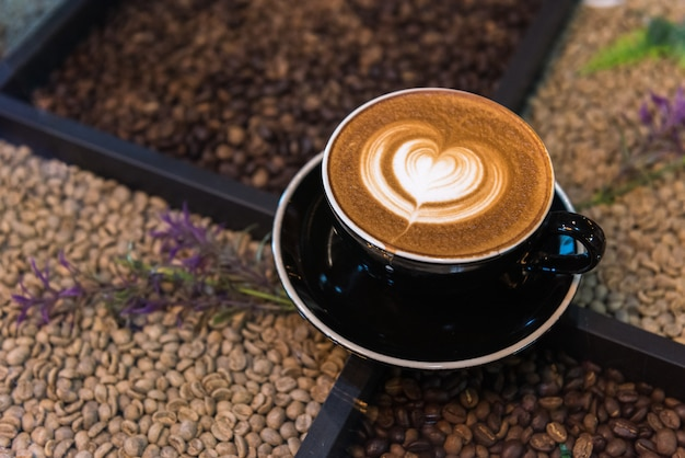 Una tazza di caffè latte art sul tavolo con chicchi di caffè
