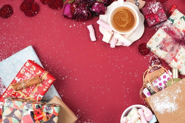 Una tazza di caffè profumato e decorazioni natalizie su sfondo rosso. regali e syootrizy per natale. vista dall'alto. telaio. copia spazio